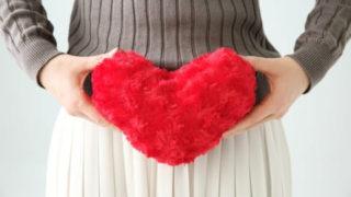 子宮の前にハートのクッションを持つ女性
